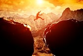 30683966-man-jumping-over-precipice-between-two-rocky-mountains-at-sunset-freedom-risk-challenge-success